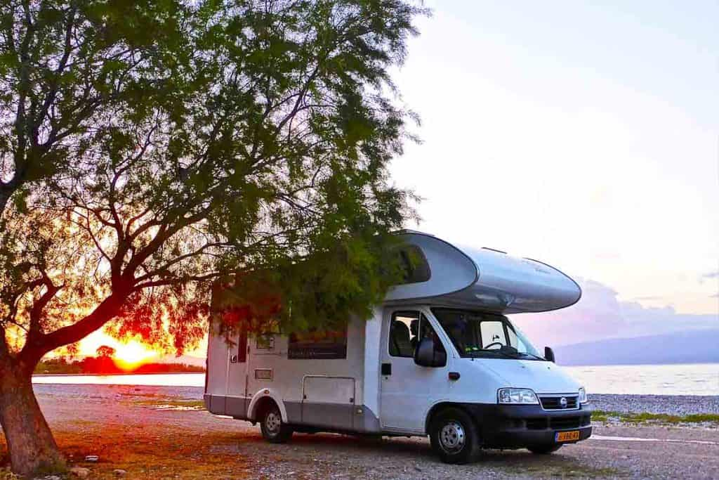 Buying a motorhome allows you to park in remote areas and spend time in nature, like the motorhome parked here by the lake.