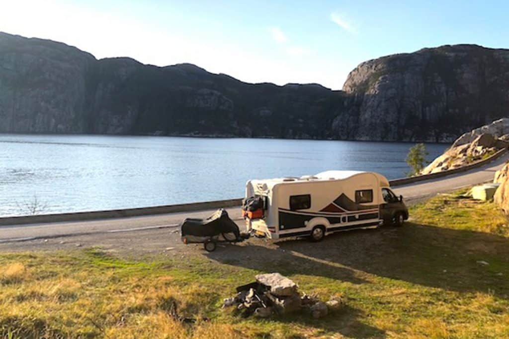A large motorhome parked in front of a picturesque lake.