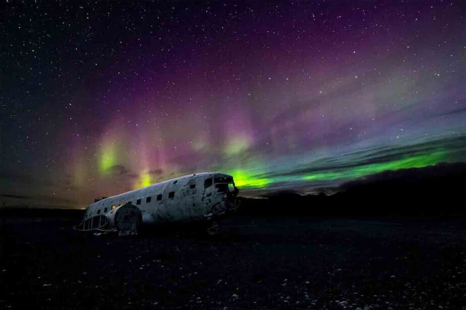 A view of the purple and green hues of the Northern Lights   in front of a plane crash in Iceland- one of the best places to see the Aurora Borealis in Europe