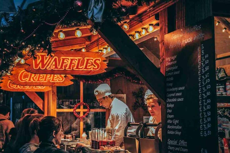 A man selling and serving waffles and crepes at a European Christmas market.