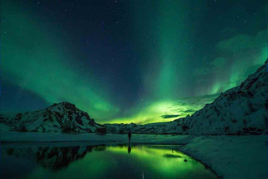 The snow covered mountains and green hues of the northern lights in Norway.