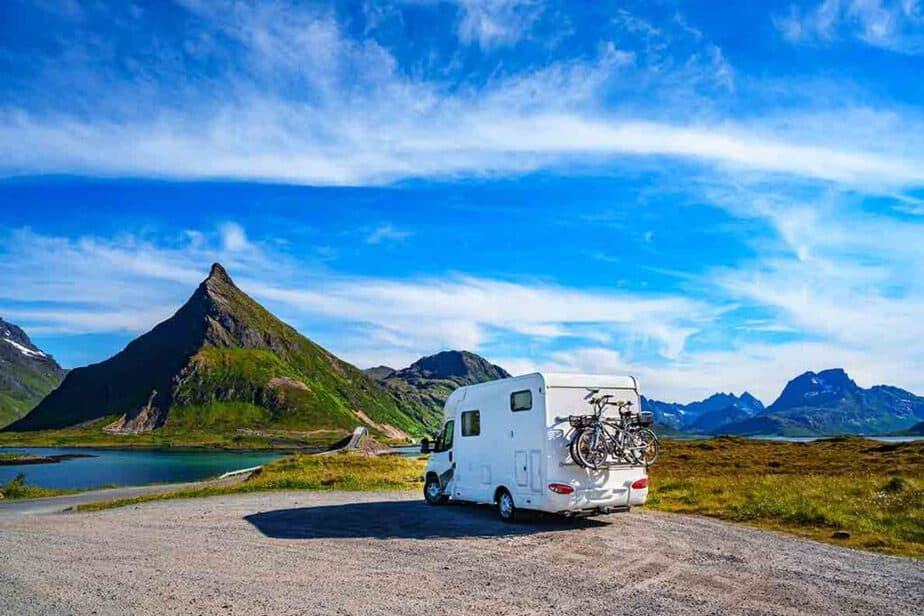 A small motorhome that is under 6m and parked in front of the mountains,
