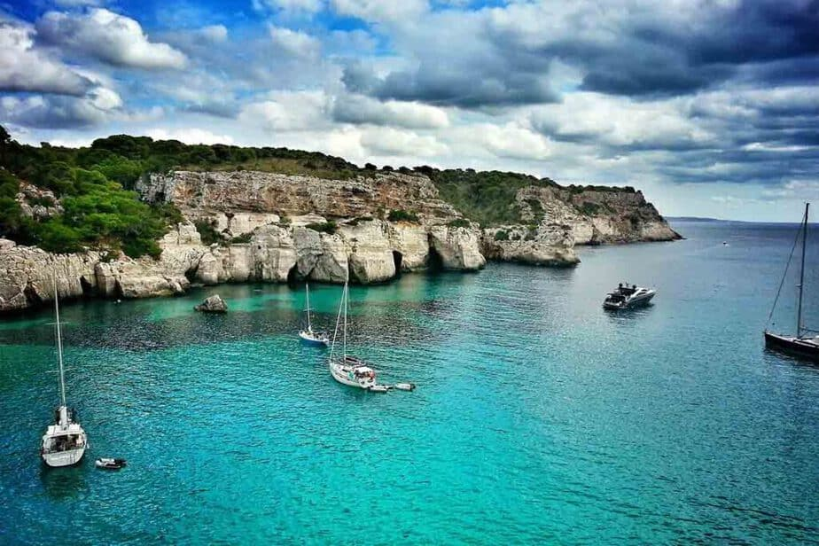 Sailboats in  the water and along the rugged coast of Menorca Spain.