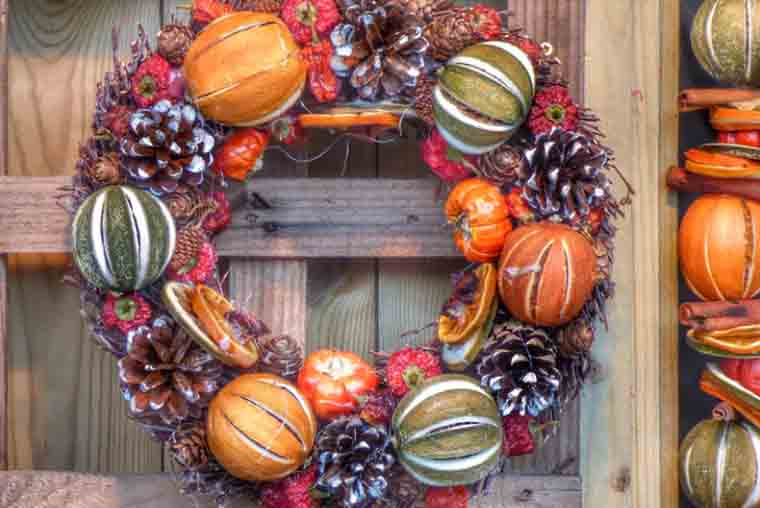 A festive holiday wreath made with pine cones and gourds.