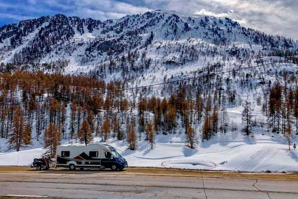 A large RV, over 3.5 tonnes, sitting in front of some snow-capped mountains.