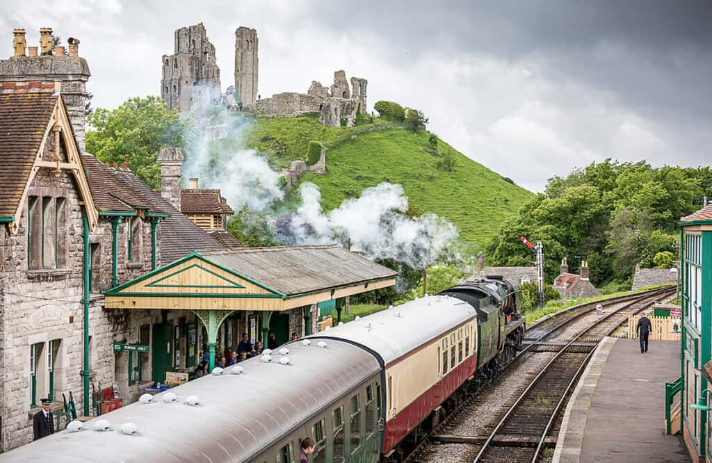 Corfe Castle Train Station and the castle in the background- one of the best places to visit in Dorset